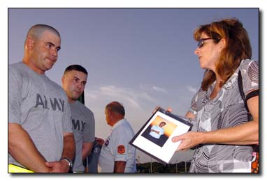 "Elizabeth Berry shows soldiers from the 189th Military Police Co. at U.S. Naval Station Guantanamo Bay, July 15, 2009, a photograph of her brother, Capt. William F. Burke Jr., a firefighter from Engine 21 who died when the north tower of the World Trade Center collapsed. Berry and her sister, Janet Roy, were part of a group of Sept. 11, 2001, victim family members who asked to meet the Joint Task Force guards -- just to say, ""thank you"" -- when the group was here for the recent military commissions proceedings."